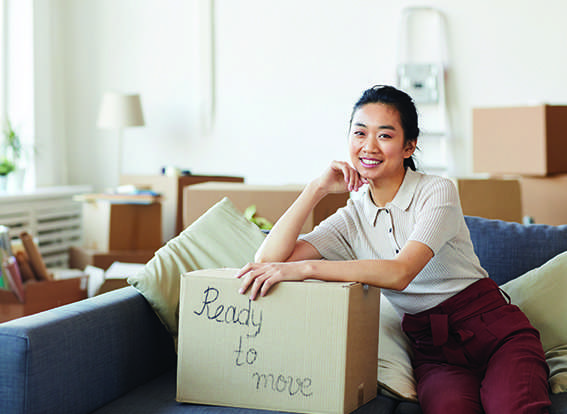Student in apartment filled with boxes ready to move in